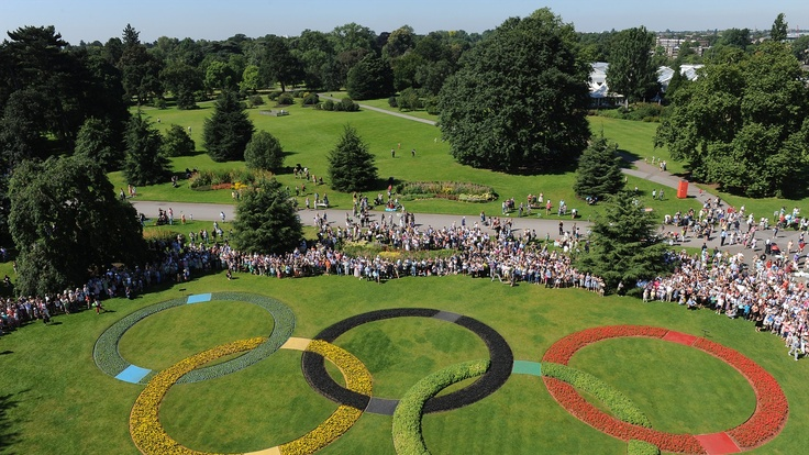 33: Oliver Golding holds the Olympic Flame in between the Olympic Rings at Kew Gardens during Day 67 of the Olympic Torch Relay.