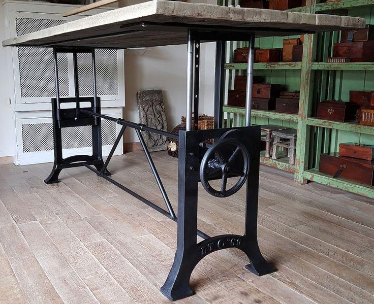 Deze in hoogte verstelbare Industriele tafel heeft een gietijzer in hoogte verstelbaar fabrieksonderstel dat in eigen werkplaats op maat gemaakt wordt. In combinatie met een mooi doorleefd tafelblad gemaakt van oud eiken wagonplanken. Verstelbaar van 76cm naar 114cm hoog.   Deze tafel kan naar wens op maat gemaakt worden. Zelfs 400 cm en langer!