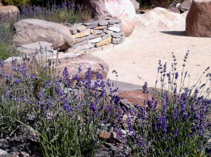 Miejsce na ognisko w ogrodzie przydomowym wg projektu PracowniaOkaz. Zastosowano: lawenda, kamień i nawierzchnia przepuszczalna Hanse Grand