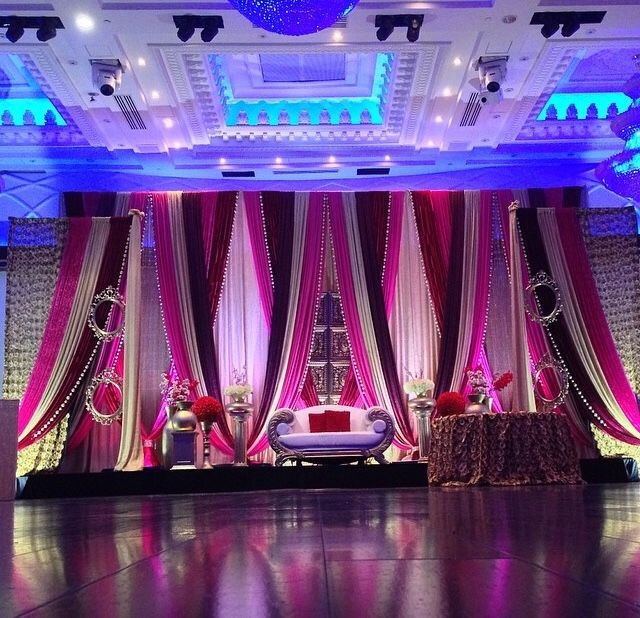 Big open dance floor with pink/red draping