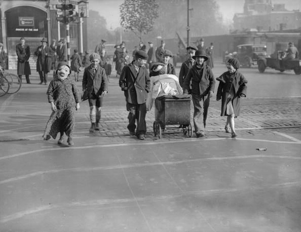 Children pushing a pram containing a guy to celebrate Guy Fawkes are using a 'pedestrian lane' in Kennington Road south London a new concept in road safety, 3rd November 1934.