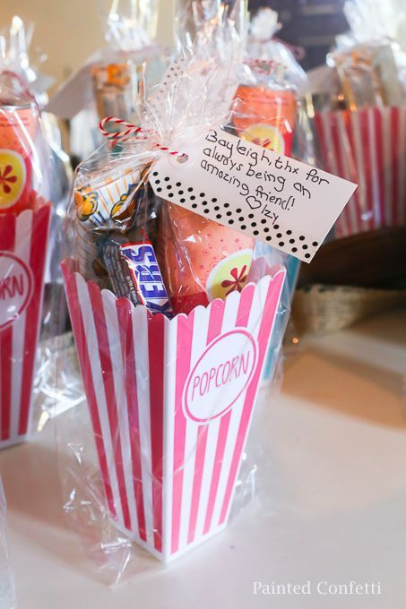 Backyard Movie Night Birthday Party Favors. Plastic popcorn boxes make the cutest take home gift. We filled ours with microwave popcorn, red box certificate, and yummy movie candies.