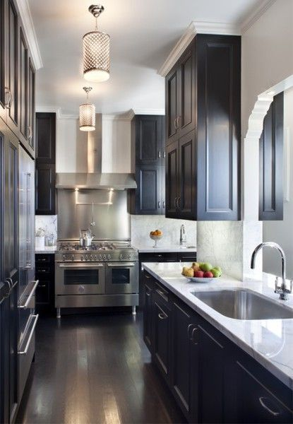 Stunning kitchen with glossy black kitchen cabinets, marble slab countertops & backsplash, gray walls paint color, crisp white moulding, silver pierced pendants and glossy espresso wood floors.