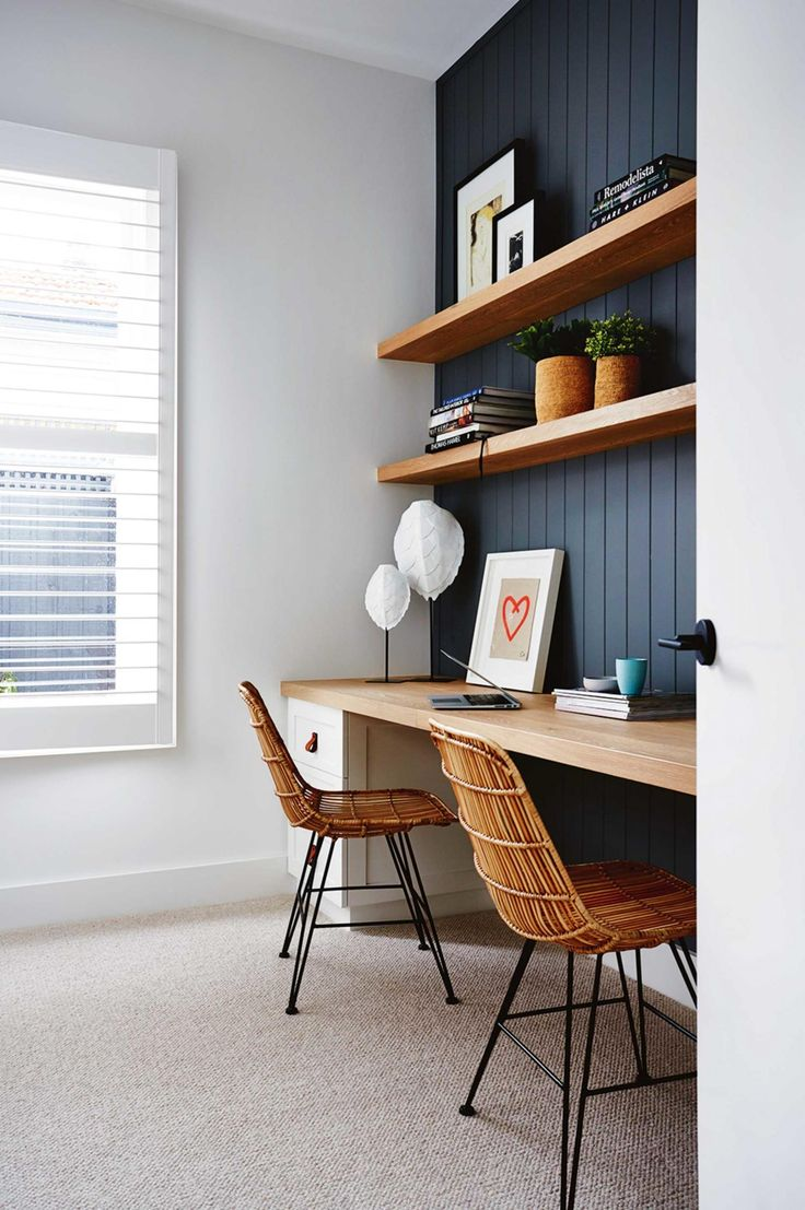 Navy paneled wall behind desks + open wood shelving + long wood desk for 2 + rattan desk chairs