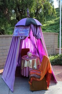 DIY fortune teller booth made out of a painted umbrella, a spherical dish, hand-dyed sheet, and patio furniture