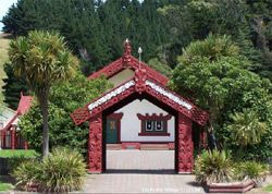 Looking towards the marae entrance-way gate. Lovely curved Maori carvings over door and window of meeting house seen in background. In East Coast, NZ.
