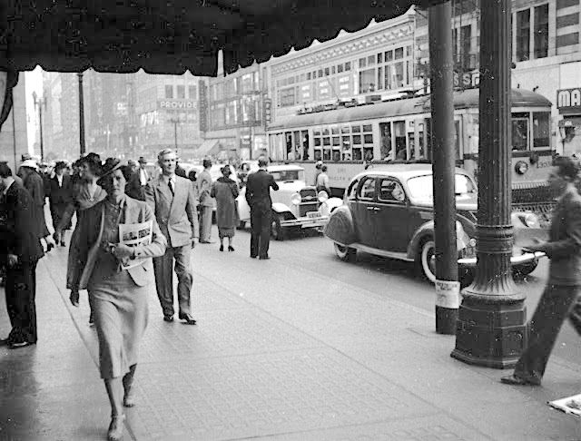 This is one of those slice-of-regular-life photos that I love to come across. In this one, we are able to catch a glimpse of life at the corner of 7th and Olive Streets, downtown Los Angeles, 1937. We're treated to aspects of 1930s life that we don't see anymore: all the women are in hats; all the men are in suits; and there's a streetcar trundling along 7th Street whisking people in and out of the city, who are glad they won't have to search for decent parking.