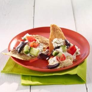 This healthy dip recipe has a Middle Eastern twist—cucumbers, tomatoes, feta and olives are layered on top of a creamy base of hummus and a touch of tangy yogurt.