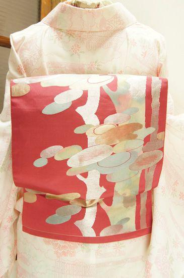 こっくりとした深みのあるローズピンク色の地に、雲母を切りばめたような虹色の樹木模様が織り出された名古屋帯です。