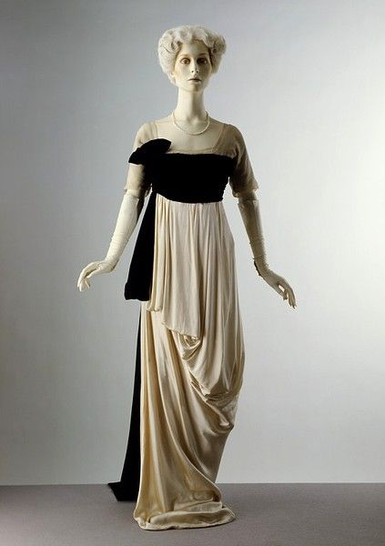 Evening dress  Place of origin: London, England (made)  Date: ca. 1912 (designed)  Artist/Maker: Lucile, born 1863 - died 1935 (maker)  Materials and Techniques: Satin, trimmed with chiffon and machine-made lace; cummerbund of silk velvet; bodice lined with grosgrain and supported with whalebone