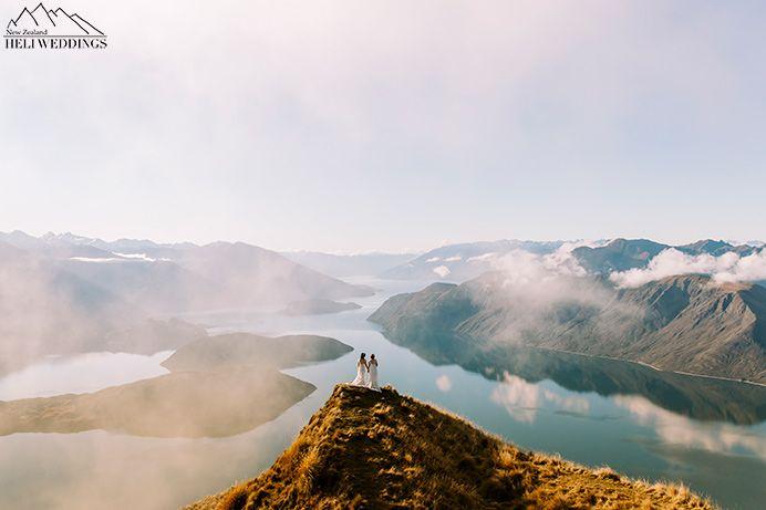 brides stand on Coromandel peak for wedding photos. Heli Wedding - Same sex wedding Wanaka New Zealand