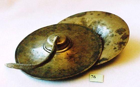 76,  Bronzen Cimbalen Tibet. 11,8 cm diameter, plaatdikte 0,1 cm. In het midden een gaatje waardoor een leren riempje zit. Om het gaatje en aan de buitenkant twee dunne lijntjes. Bronskleurig. lama [religie] (Tibetaans, eigenlijk bla-ma = leraar), in Tibet, Mongolië en China de naam van een boeddhistisch geestelijke; stemt als zodanig overeen met het Sanskrit goeroe (zie lamaïsme).