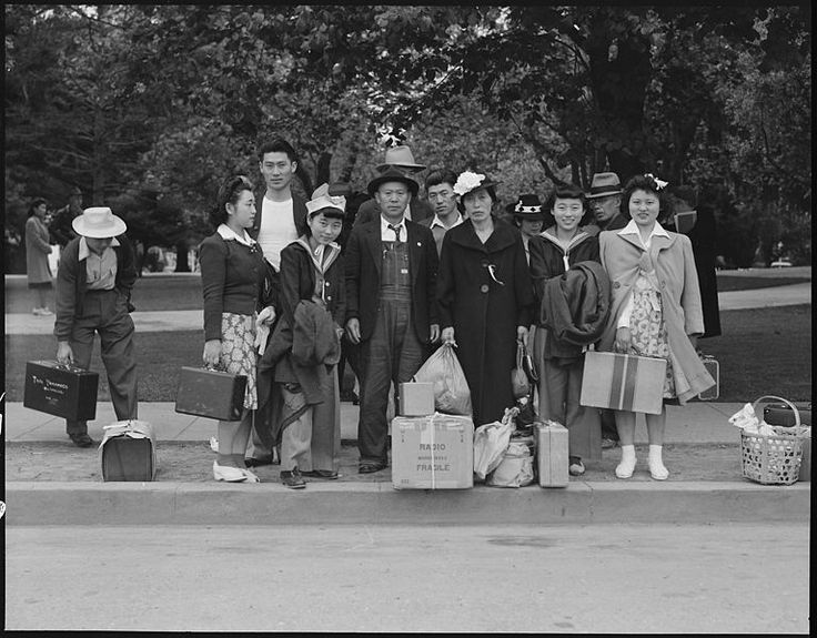Family awaits evacuation bus, Hayward, California, 8 May 1942, Dorothea Lange, public domain via Wikimedia Commons.