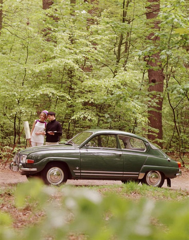 SAAB 96, full trim, greens in the forest.  Great Period Advertising Shot. A Swedish car / Swedish Girl and the whole forest to yourself.