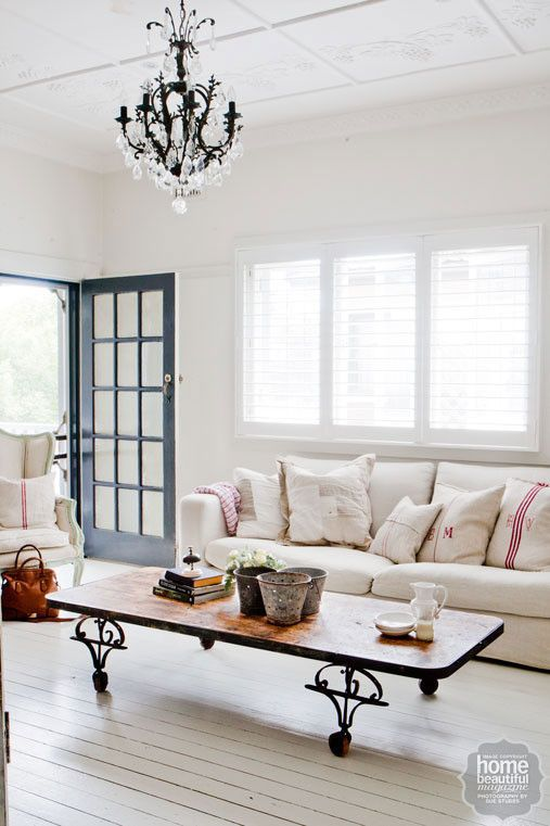 Painted white floors give a country cottage feel to this living room, while a chandelier adds a touch of glamour.