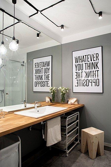 Inspiração de decor industrial no banheiro. Eis a receita pro sucesso: parede cinza, quadro com frase em preto e branco, iluminação com fiação aparente e bancada de madeira.