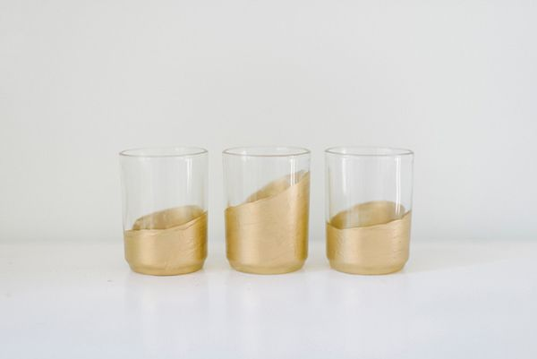 "DIY Golden Votives -- plain, inexpensive glass votives + metallic gold paint:  ""These votives are absolutely gorgeous at night – glowing and glistening, each in a slightly unique fashion! We especially love the uneven edges of the votives that create a more hand-painted feel. Easy to create and the perfect way to jazz up traditional votives!"""