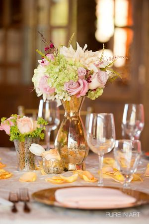 Short Gold Vases With Pink Roses And White Flowers For Centerpieces Surrounded By Orange Flower Petals A Modern Meets Vintage Indoor Wedding Reception