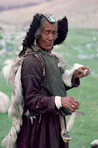 A woman yak herder wears a red & turquoise head-dress (perak), spins yak wool whilst watching the herd. Nimaling Plateau. Ladakh. India. #NomadsSecrets