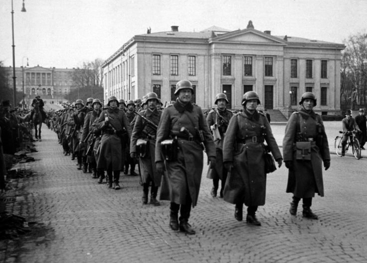 German soldiers march in formation down Oslo's main street, Karl Johans Gate, following their successful invasion and occupation of Norway. In the far background can be seen the Norwegian Royal...