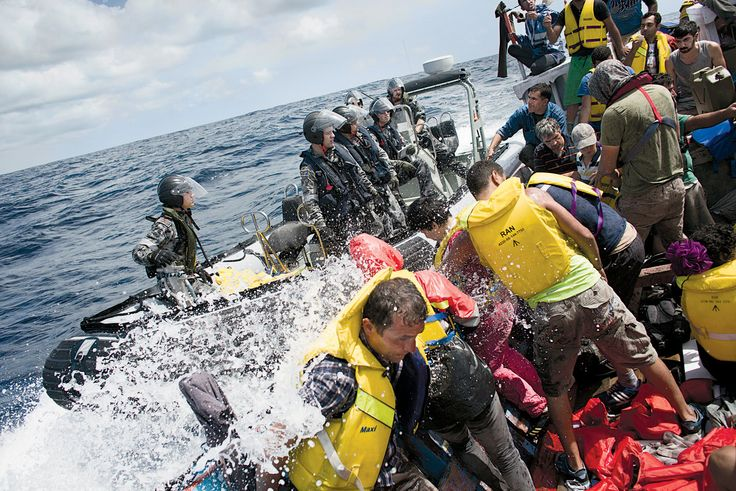 Nearing Christmas Island, the boat was met by sailors from the Australian Navy. The asylum seekers pleaded with Australian sailors to take a suffering passenger aboard. PHOTOGRAPHS BY JOEL VAN HOUDT
