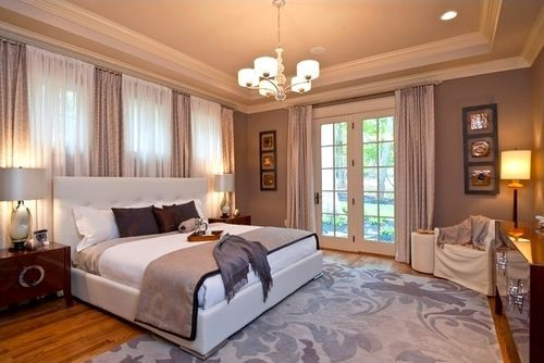 Curtains behind bed in front of windows