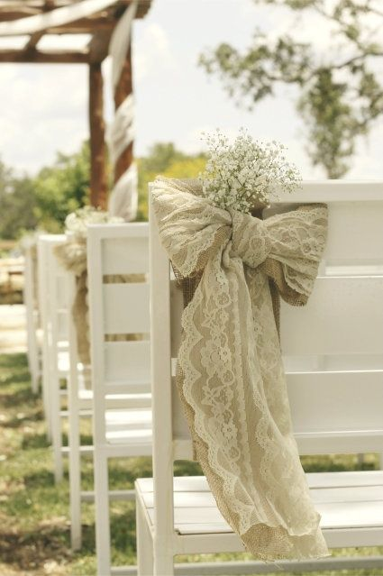 Burlap, lace, and baby's breath bow wedding aisle decor. Simple, rustic elegance; also example of how to secure decor piece on simple pews (ones without an obvious edge perfect for hanging decor from)