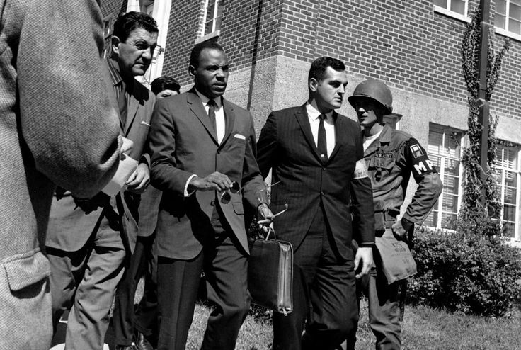 Chief U.S. Marshal James McShane, left, and an unidentified marshal at right escort James Meredith, center with briefcase, to the University of Mississippi campus in Oxford, Mississippi, on October 2, 1962. Meredith, was the first black student to attend the University of Mississippi after integration.