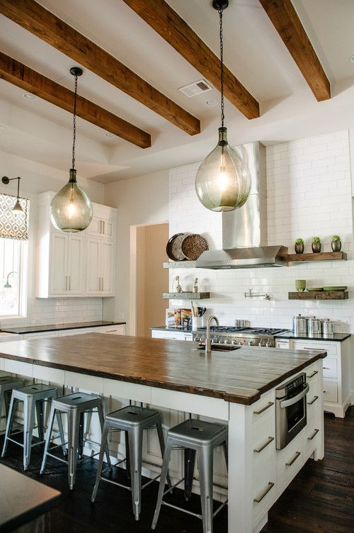 Love this white kitchen with wood beams and hanging pendant light fixtures.
