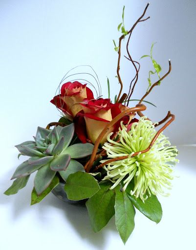 Asian-inspired arrangement with succulents, chrysanthemum, roses, and curly willow tip.