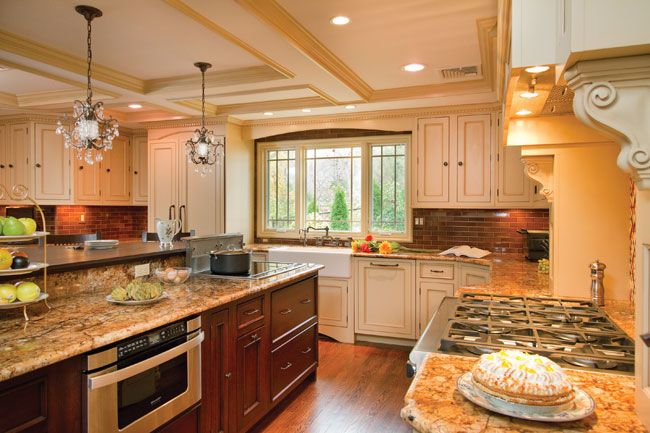 A kosher kitchen designed for multiple cooks. Cream cabinets with a dark island. And a microwave drawer.