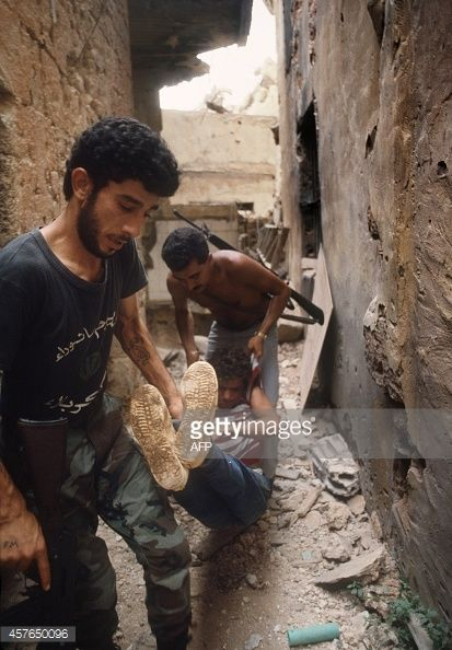 Two militiamen loyal to the pro-Syrian Amal movement, the first political organization of Lebanon's Shi'ite Moslems, evacuate 17 August 1985 in west Beirut a injured Amal fighter as part of their...