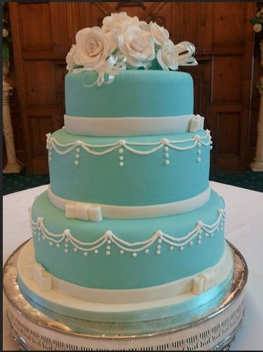 3-tier tiffany blu with white swoop filigree and small white fondant ribbon and bow trim at base of each layer white rose bouquet on top