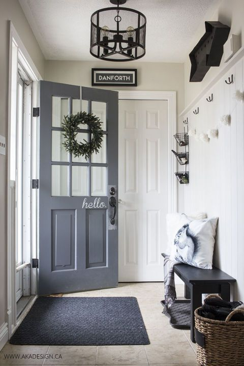 "What better way to greet your guests than by spelling out ""hello"" on your front door? This modern entryway was softened for summer with a green wreath and a pom-pom banner.  See more at AKA Design."