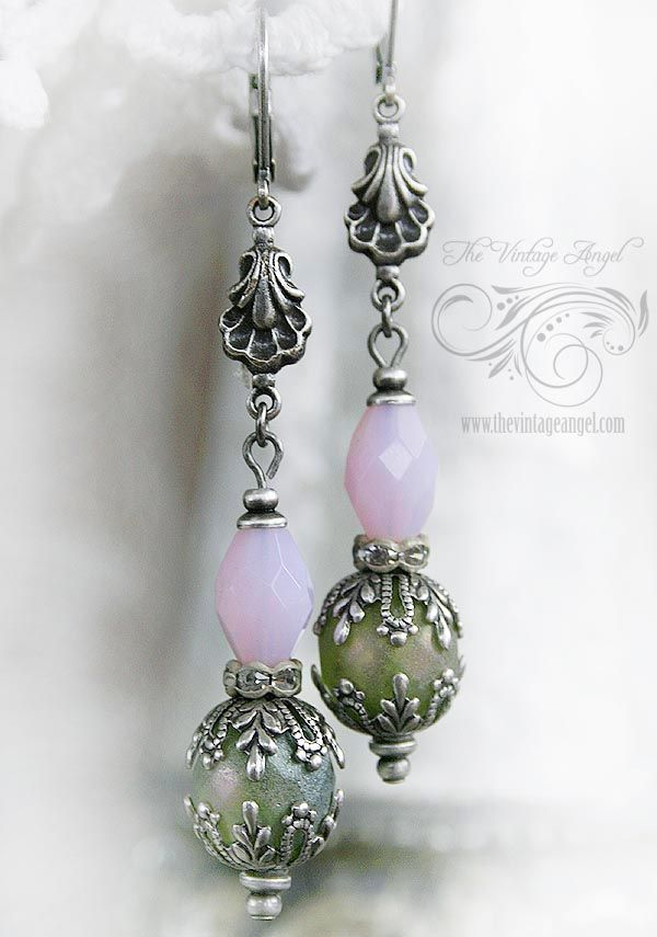 Inspired by the colors in a shabby chic garden, these Czech glass and antiqued silver earrings are playful and elegant.  Large, sage green (with a hint of mauve) Czech glass frosty beads are accented with darkened silver garden themed bead caps, rhinestone rondelles and pale opaque pink oval beads.  The assembly is hung from pretty vintage inspired connectors and leverback hooks in aged sterling silver plated brass for pierced ears.    All components are American-made brass with ster