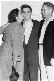 Elvis gets a kiss from him mom, Gladys... his dad Vernon looks on.