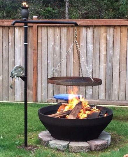My custom swinging fire pit/BBQ cooking grate. the cooking grate raises and lowers manually with the winch and rotates 360 degrees!!                                                                                                                                                                                 More