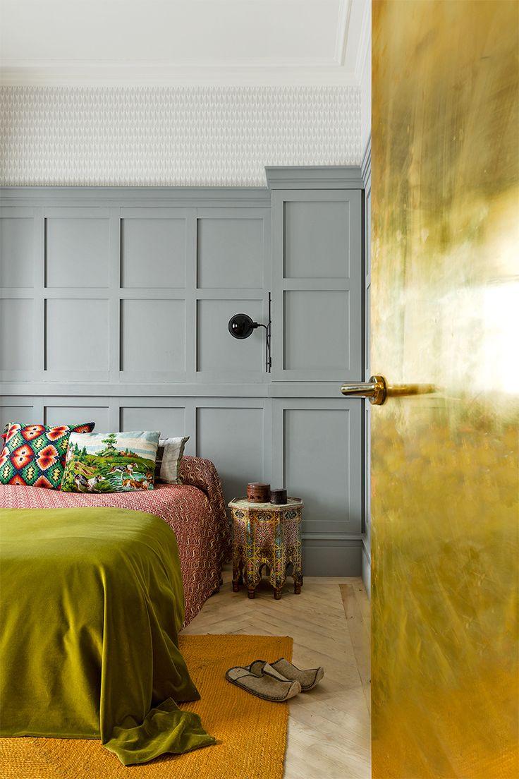 Al dormitorio se accede por una puerta forrada en latón. Paredes de madera con aplique Funiculí de Marset, mesita marroquí años 20, colcha con tela verde de Güell-Lamadrid y otra africana, y cojines de petit point y bordados húngaros de los 40.