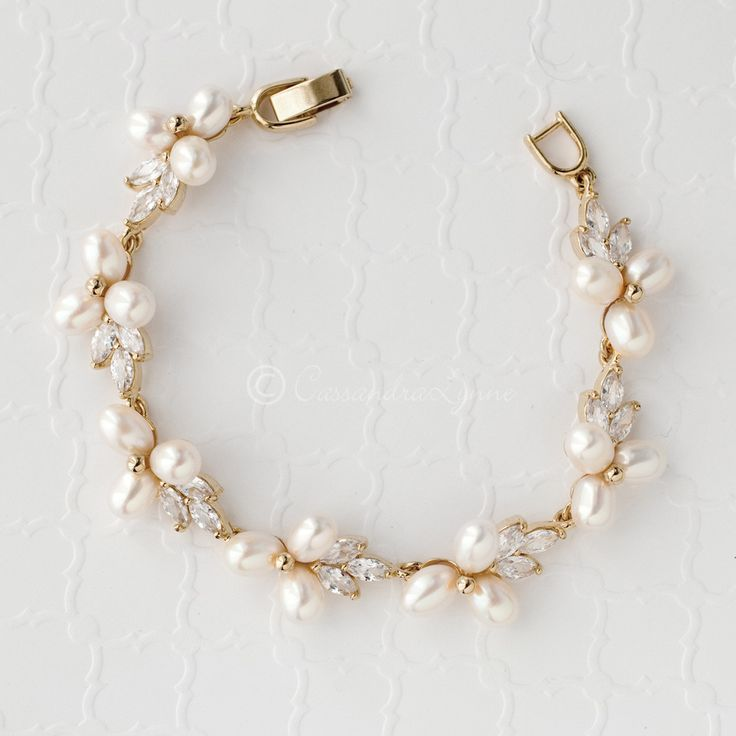 This lovely bracelet is designed with ivory oval, glass pearl flowers and sparkly CZ leaves. Dainty and delicate for your wedding day! Locking clasp, 7 inches l