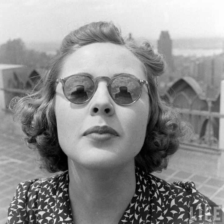 excellence w/tiny curls in the hair, round sunglasses, printed bouse