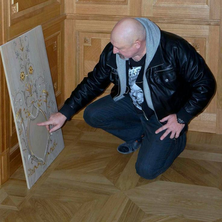 Виктор Иванов с художниками студии (не вошли в кадр) разбирают образец на фоне деревянных панелей в последствии которые будут расписаны.