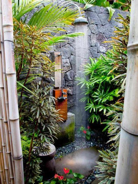 douche de jardin en inox entourée de plantes tropicales et fleurs roses