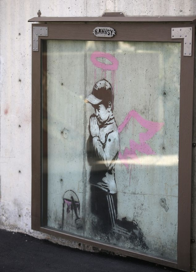 A Banksy image of a silhouette of a boy kneeling and praying is on a wall outside a parking garage in Park City, Utah