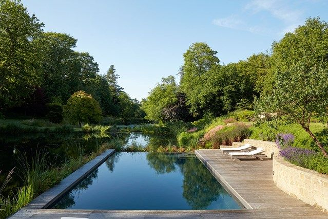 Country Garden Infinity Pool with Decking in Garden Swimming Pool Ideas. This Family home in a restored and modernised barn has an infinity pool with decking and sun loungers.