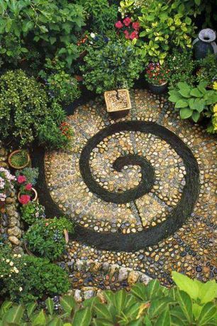 Eclectic Landscape/Yard with exterior stone floors, DIY Spiral Rock Pebble Mosaic Path, Dawns Early Light Hosta, Raised beds
