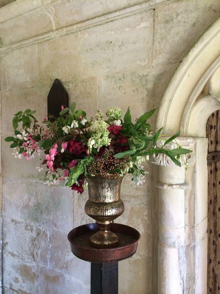 Seasonal spring wedding flowers arrangement of crab apple blossom, parrot tulip, kloon ranunculus, Solomon seal, photinia, exchorda, dicentra