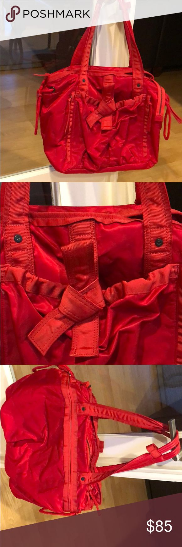 """Large Gorgeous Red Lululemon Athletica Sports Bag Great Lululemon red sports bag. Very good used condition.   Small mark on side where it looks like the bag rubbed against something light and a water looking stain around 6 1/2 long and 1"""" wide. Never noticed it until I examined the Bag closely. Inside of bag is spotless and includes a bag that folds inside. Approximately 13 1/3"""" H x 19"""" W and 6 1/2"""" D lululemon athletica Bags Totes"""