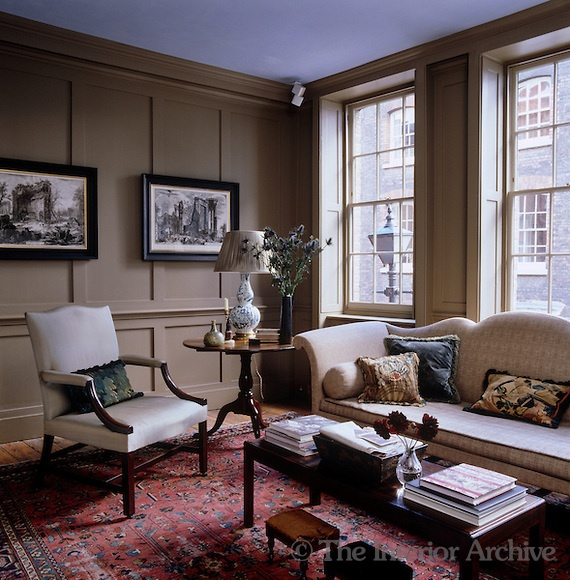 A pair of 18th century engravings hangs on the panelled wall of the drawing room which is furnished with a George II armchair and a camel-back sofa