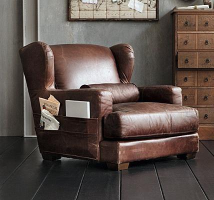 Der niedrige Ohrensessel mit extra tiefer Sitzfläche hat einen Bezug aus braunem Used-Leder. Der Vorteil des Vintage-Bezugs: wenn neue Kratzer hinzukommen...