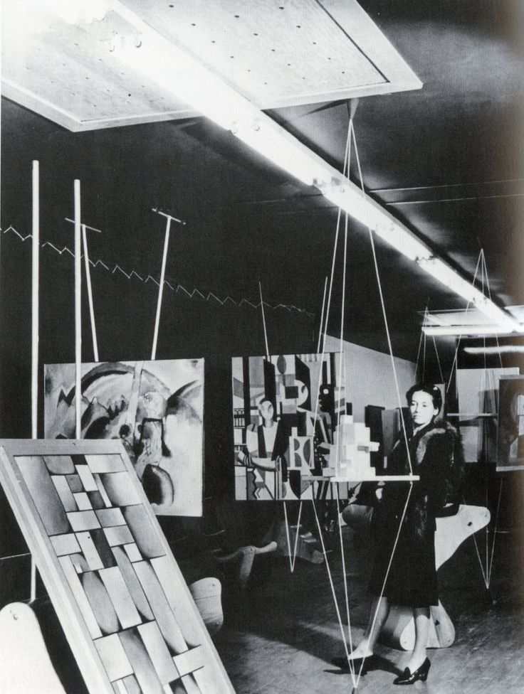 Peggy Guggenheim in her Art of This Century gallery, New York City, 1942—installation design by Frederick Kiesler - everything hung from beams in this room.